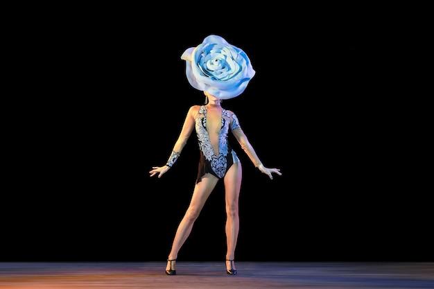 Zachwycony. młoda tancerka z ogromnym kwiatowym kapeluszem w neonowym świetle na czarnej ścianie.
