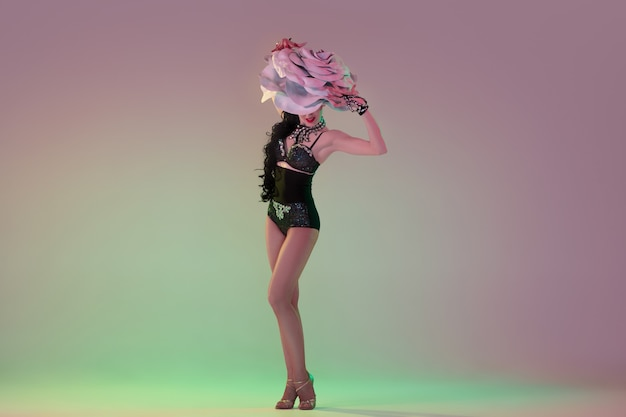 Zachwycony. młoda tancerka z ogromnymi kwiatowymi kapeluszami w neonowym świetle na ścianie gradientowej.