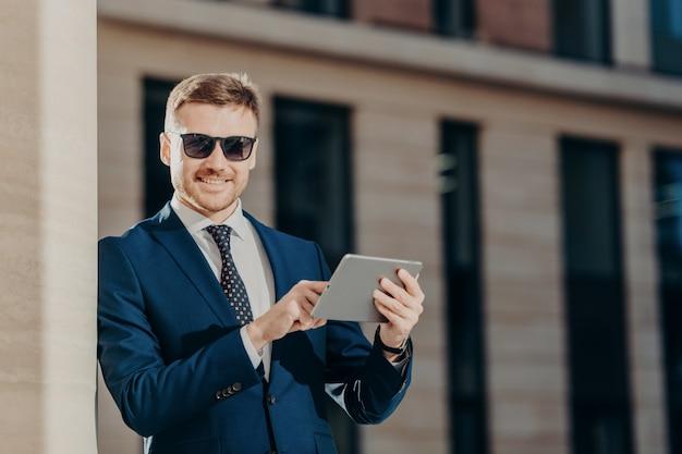 Zachwycony młody biznesmen z panelem dotykowym w internecie