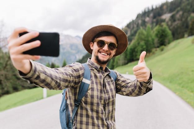 Zachwycony młody człowiek w modnej kraciastej koszuli spędzający czas na świeżym powietrzu, rano zwiedzając okolicę