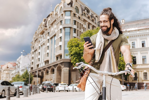 Zachwycony pozytywny człowiek patrząc na swój gadżet podczas jazdy na rowerze