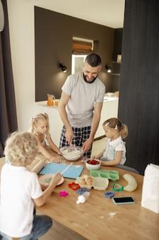 Zachwycony pozytywny człowiek przygotowujący omlet dla swoich dzieci