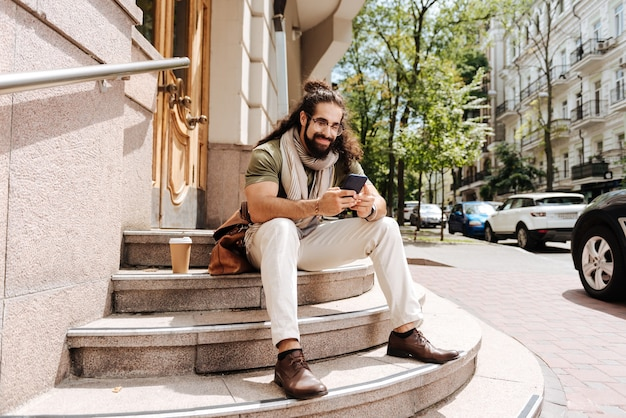 Zachwycony przystojny mężczyzna piszący wiadomość siedząc na schodach ze swoim smartfonem