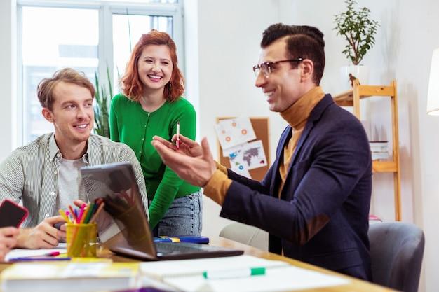 Zachwycony wesoły mężczyzna uśmiechający się podczas rozmowy o biznesie ze swoimi uczniami