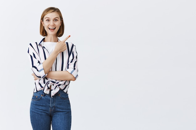 Zaciekawiona i zaintrygowana atrakcyjna dziewczyna spotyka interesującą promocję, wskazując prawy górny róg