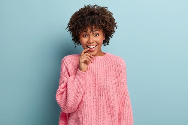 Zaciekawiona szczęśliwa kobieta trzyma palec wskazujący na ustach, patrzy z zadowolonym wyrazem twarzy, słucha najświeższych wiadomości od przyjaciela