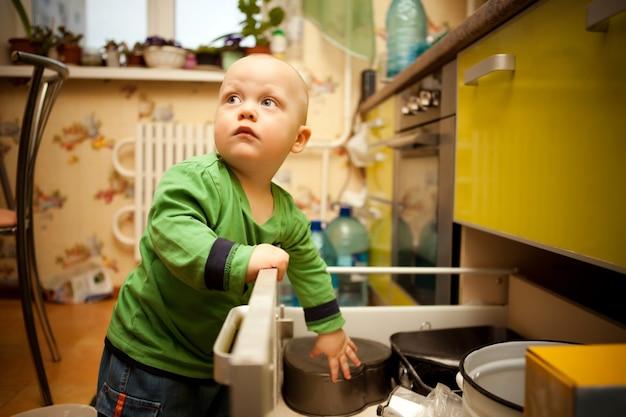 Zaciekawione dziecko w zielonym swetrze otwiera kuchenną szufladę z naczyniami. chłopiec z dużymi niebieskimi oczami odwraca wzrok