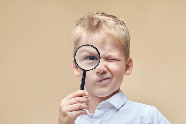 Zaciekawiony chłopiec patrzy na przód przez szkło powiększające i krzywi się.