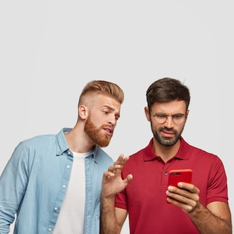 Zaciekawiony facet z rudą fryzurą i brodą zagląda do smartfona swojego przyjaciela