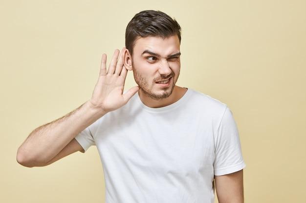 Zaciekawiony młody człowiek z włosiem trzymający rękę przy uchu, podsłuchujący, podsłuchujący sekret, mający skoncentrowany wyraz twarzy, próbujący usłyszeć wszystko. koncepcja plotki i plotki