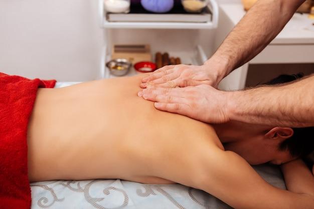 Zacieranie szyi. doświadczony męski mistrz z owłosionymi rękami pracuje z tylnym sercem kobiety, podczas gdy ona spokojnie odpoczywa
