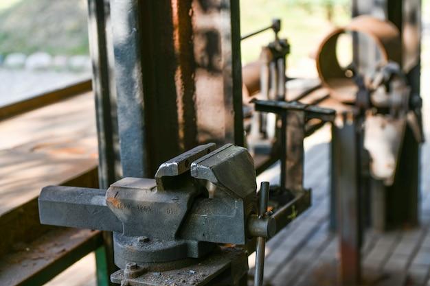 Zacisk kowala. metalowe urządzenie mocujące na starym stole warsztatowym
