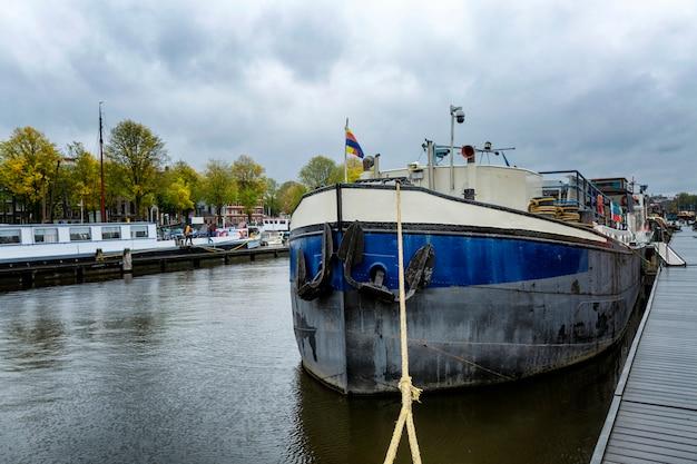 Zacumowany stary statek przy nabrzeżu. tradycyjny hotel wodny w amsterdamie.