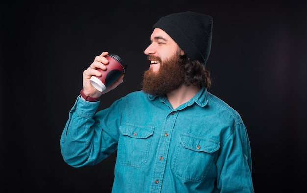 Zacznij dzień od filiżanki kawy, brodaty hipster delektuje się porannym cappuccino