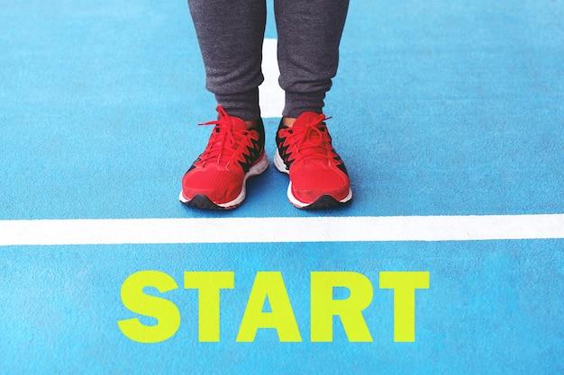 Zacznij od lekkoatletycznego męskiego joggingu na linii startu po asfalcie bieżni stadionowej przygotowującej się do bieżni.