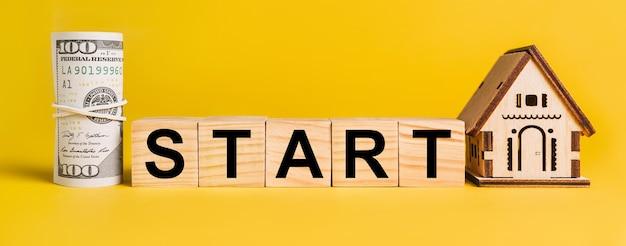 Zacznij od miniaturowego modelu domu i pieniędzy na żółtej powierzchni. pojęcie biznesu, finansów