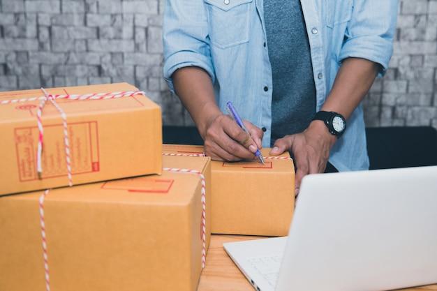 Zaczyna małego biznesowego przedsiębiorcy sme lub freelance azjatykci mężczyzna pracuje z pudełkiem w domu c