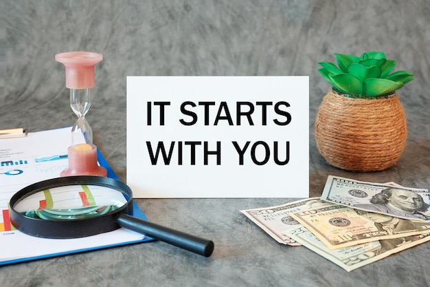 Zaczyna się od ciebie jest napisane w dokumencie na biurku z akcesoriami biurowymi, pieniędzmi, schematem i lupą