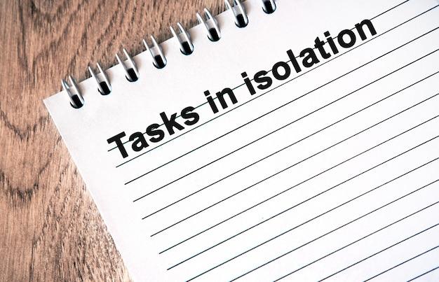 Zadania w izolacji - czarny tekst na białym notesie z liniami na drewnianym stole