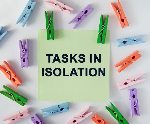 Zadania w izolacji - tekst na kartce notatek i kolorowe spinacze do bielizny