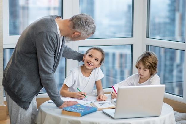 Zadanie domowe. ojciec pomagający dzieciom w lekcjach i wyjaśniający im coś