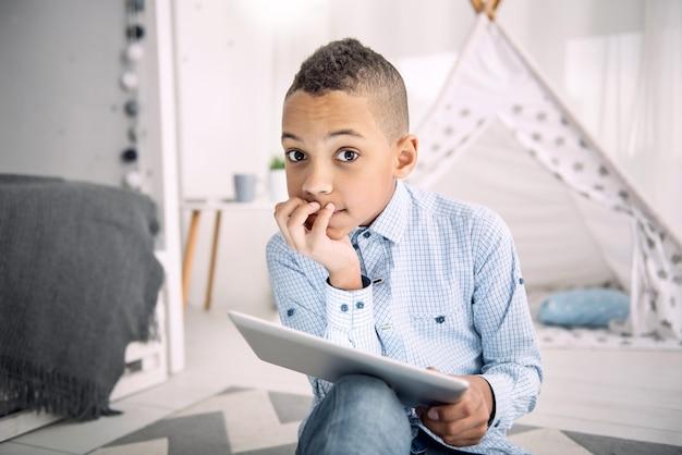 Zadanie online. pączkujący chłopiec afroamerykański patrząc na kamery podczas korzystania z tabletu