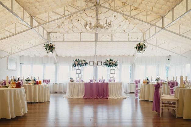 Zadaszona sala na przyjęcia weselne ze stołami i dekoracjami kwiatowymi
