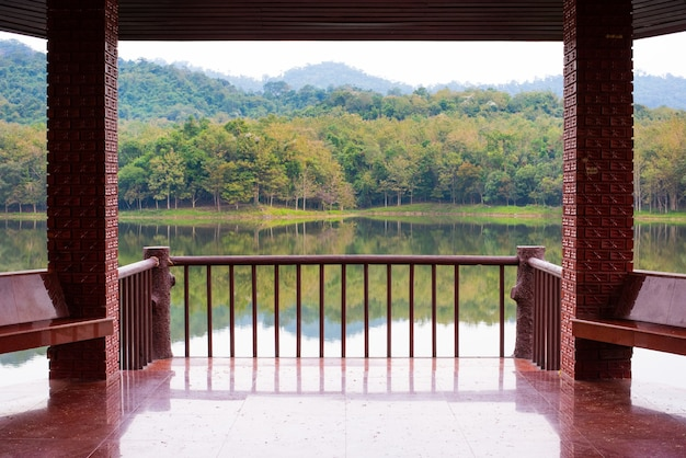 Zadaszony taras z ceglanymi kamiennymi filarami i posadzka ogrodzona płytkami, otoczony zielenią i rzeką w słoneczny letni dzień