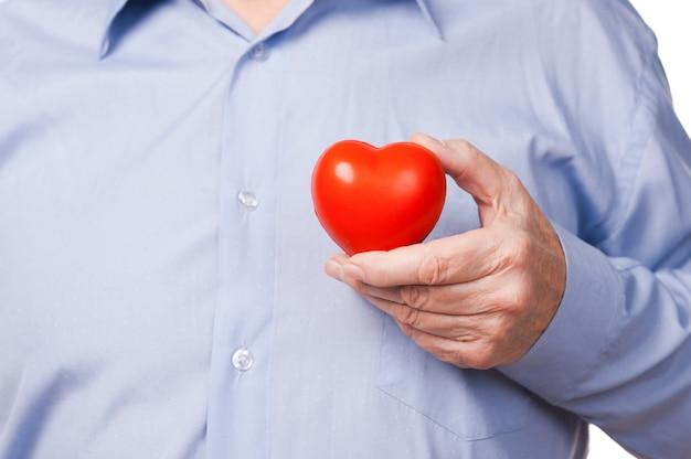 Zadbaj o swoje serce! zbliżenie starszego mężczyzny w koszuli trzymającego rekwizyt serca, stojąc na białym tle