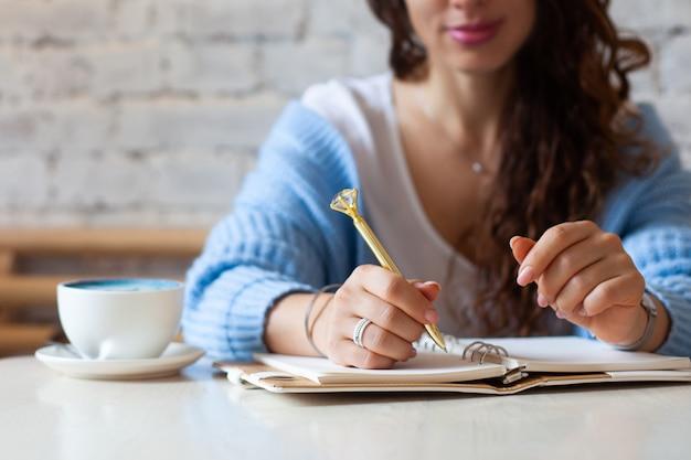 Zadbana kobieta ręka trzyma złoty długopis i zapisuje notatki złotym piórem w notesie podczas picia niebieskiej latte obok okna. niezależny dziennikarz pracujący w domu. planowanie przyszłej koncepcji. skopiuj miejsce