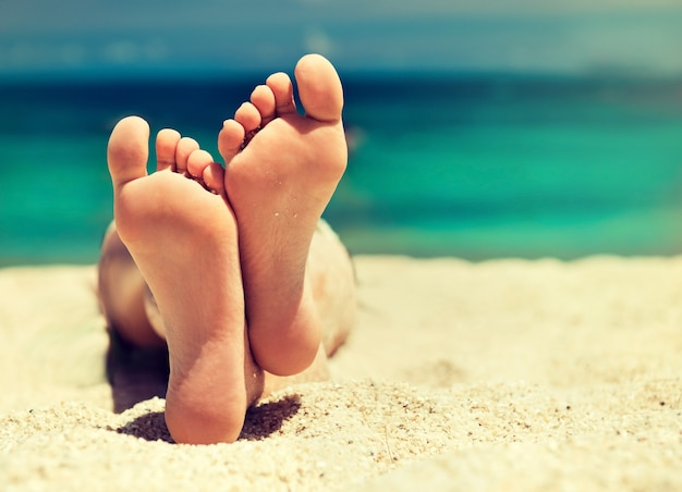 Zadbane stopy kobiety leżą na piasku tropikalnej plaży.