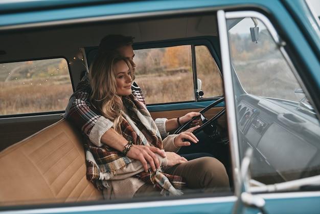 Żądna przygód para. piękna młoda para obejmując i uśmiechając się siedząc w niebieskim mini vanie w stylu retro