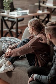 Żadnego pragnienia mówienia. nastolatek z załamaniem nerwowym siedzi na kanapie i nie ma ochoty rozmawiać