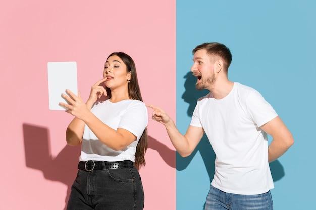Żadnego selfie. próbuje zwrócić jej uwagę. młody, szczęśliwy mężczyzna i kobieta w ubraniu na różowej, niebieskiej ścianie dwukolorowej. pojęcie ludzkich emocji, mimiki, relacji, reklamy. piękna para.