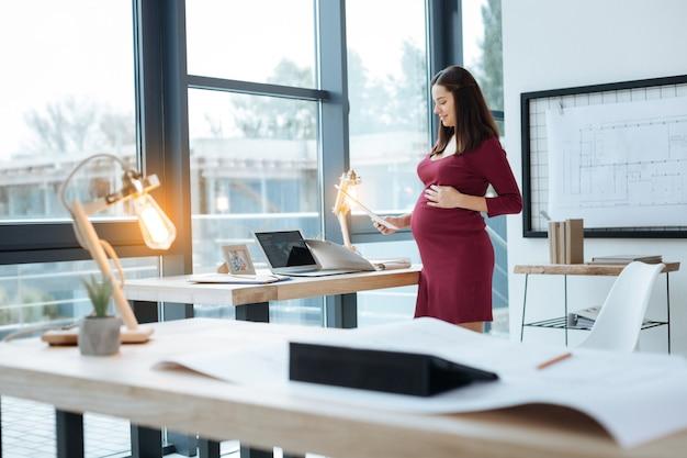 Żadnej wolnej chwili. wesoła kobieta w ciąży czytająca ważne dokumenty, stojąc przy stole i dotykając brzucha