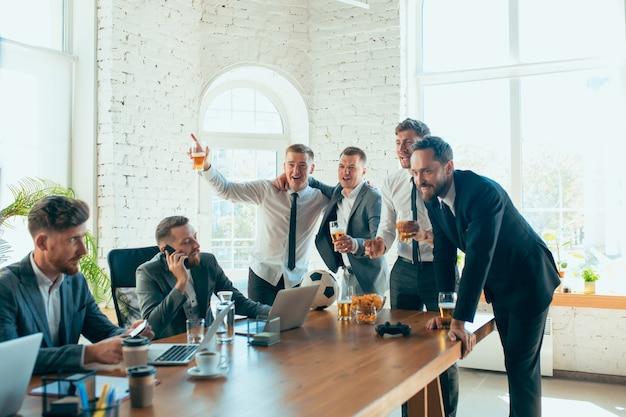 Zadowoleni, beztroscy koledzy bawią się w biurze, podczas gdy ich współpracownicy ciężko pracują i bardzo skoncentrowani.