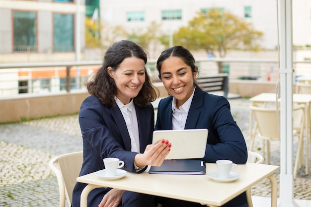 Zadowoleni bizneswomany z pastylka komputerem osobistym w plenerowej kawiarni