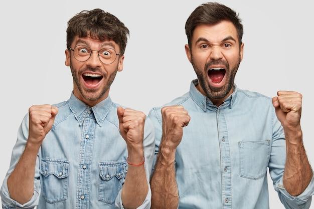 Zadowoleni fani futbolu męskiego krzyczą w imieniu swojej ulubionej drużyny, zaciskają pięści, radują się ze zwycięstwa, ubrani w dżinsowe koszule, odizolowani na białej ścianie. dwóch wesołych towarzyszy świętuje coś