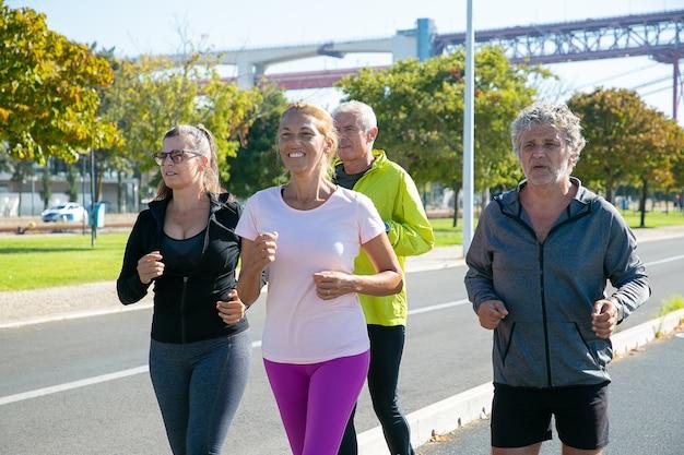 Zadowoleni i zmęczeni dojrzali biegacze w sportowych ubraniach biegają na zewnątrz, trenują do maratonu, cieszą się porannym treningiem. emeryci i koncepcja aktywnego stylu życia