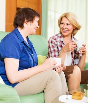 Zadowoleni koledzy picie kawy i rozmowy podczas przerwy na lunch
