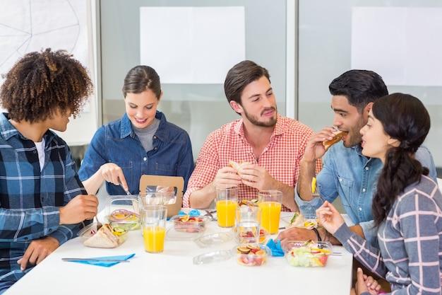 Zadowoleni menedżerowie współpracujący przy śniadaniu