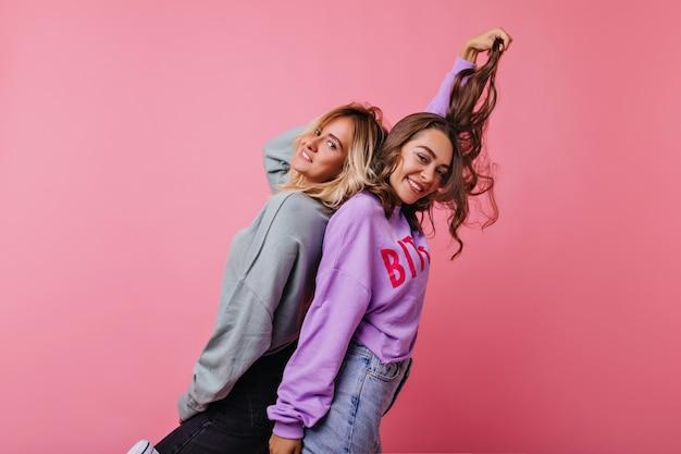 Zadowoleni najlepsi przyjaciele, którzy razem się bawią. zrelaksowana brunetka bawi się swoimi ciemnymi włosami podczas relaksu z siostrą.