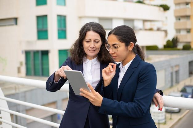 Zadowoleni przedsiębiorcy korzystający z komputera typu tablet