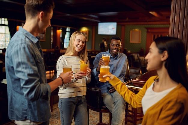 Zadowoleni przyjaciele z piwem wznoszą toast przy ladzie w barze