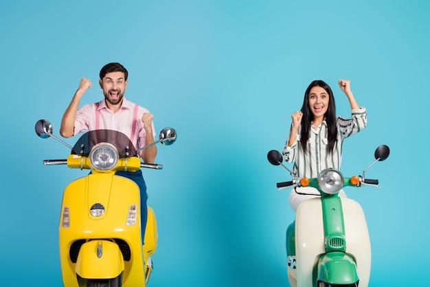 Zadowoleni szaleni dwie osoby szczęśliwa żona mąż miłośnicy sportów ekstremalnych świętują loterię na skuterze elektrycznym siedzieć podnosić pięści krzyczeć tak nosić różową koszulę w paski odizolowaną na niebieskiej ścianie