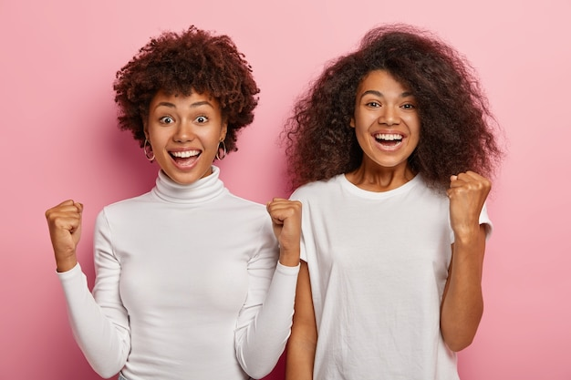 Zadowoleni, szczęśliwi dwaj stundenci z włosami afro, z podniesionymi rękami, z powodzeniem zaciskający pięści