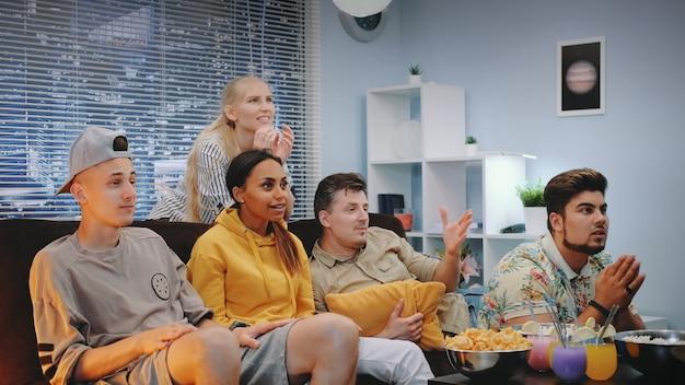 Zadowoleni widzowie oglądają sport w telewizji i rozlewają popcorn, gdy drużyna zdobywa bramki