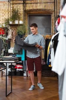 Zadowolenie. pozytywny młody człowiek uśmiecha się i czuje się zadowolony będąc w sklepie z modną odzieżą i patrząc na szary t shirt