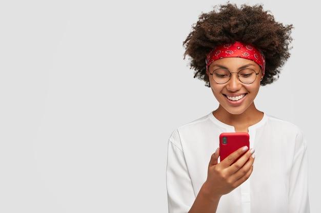 Zadowolona afrykanka z czarującym uśmiechem, śmieje się, trzyma czerwony telefon komórkowy