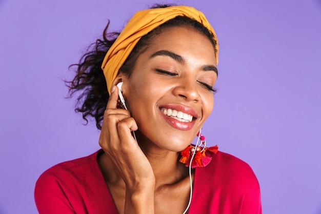 Zadowolona afrykańska kobieta w sukience słuchająca muzyki przez słuchawki z zamkniętymi oczami na fioletowej ścianie